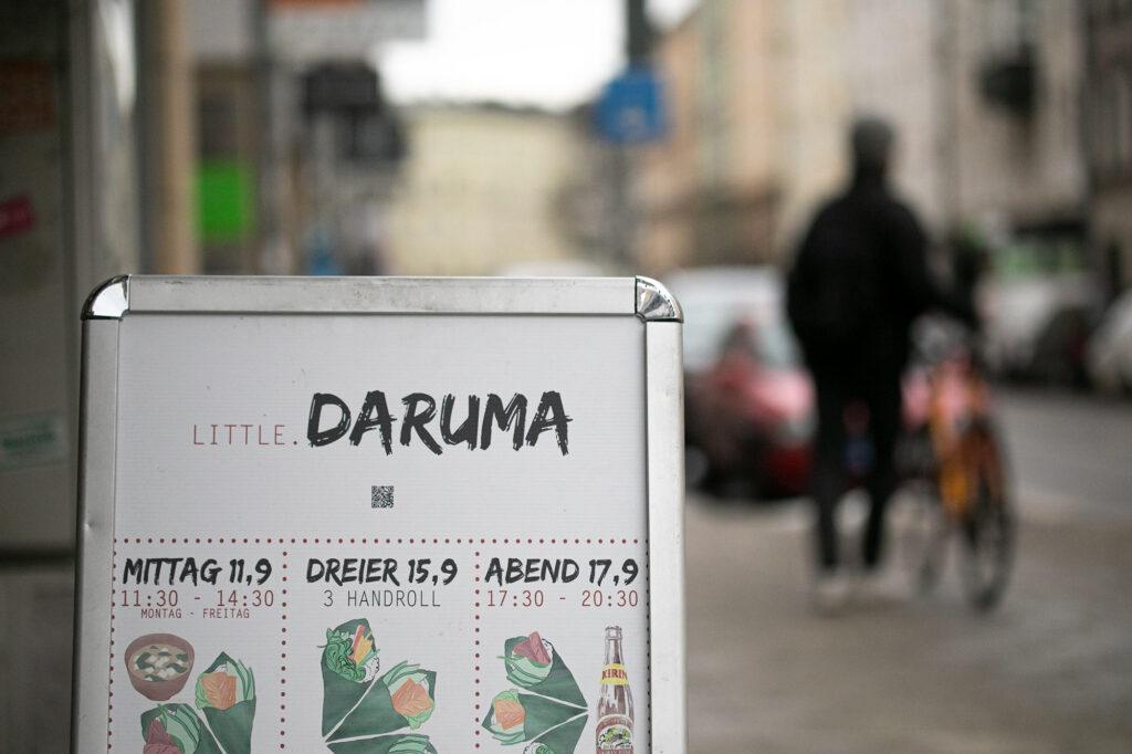 Ein Straßenszene vor dem Little Daruma mit Aufsteller