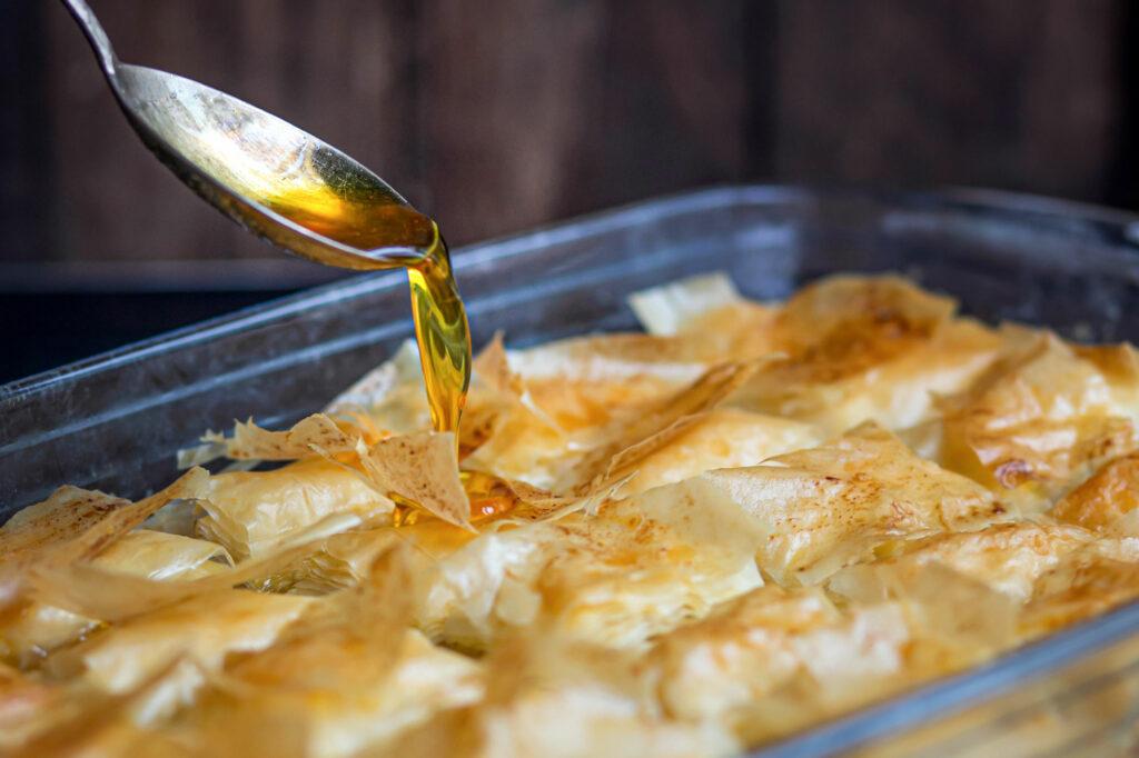 das Baklava wird mit Honig-Sirup übergossen.